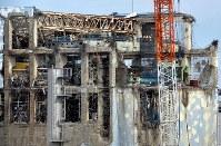 東京電力福島第1原発事故で建屋が吹き飛んだ4号機の上で作業する人たち=福島県大熊町で2012年2月20日、小林努撮影