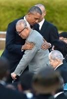 平和記念公園での演説後、米捕虜被爆者の調査をする森重昭さんを抱きしめるオバマ米大統領。手前は坪井直・日本被団協代表委員=広島市中区で2016年5月27日、久保玲撮影