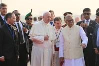 ハミド大統領(右)の出迎えを受けるフランシスコ・ローマ法王=ダッカの国際空港で2017年11月30日午後3時17分、金子淳撮影