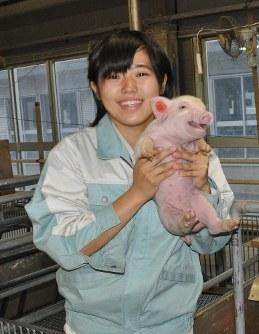 子豚を抱く石川莉凪さん=中央農業高校で2017年11月4日午後4時23分、長真一撮影