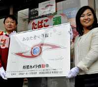 ウルトラ警備隊のマークをあしらったステッカーのデザインを持つ兵庫県尼崎市の稲村和美市長(右)ら=同市で2017年11月29日、田辺佑介撮影