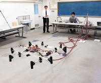 ケーブル給電のマルチコプターを飛行させる今津篤志講師(奥左)ら=大阪市住吉区杉本3の大阪市立大で、関野正撮影