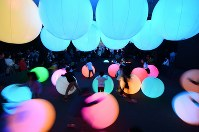 転がすと色と音が変化する光のボールで遊ぶ子どもたち=神戸市中央区で2017年11月23日、大西岳彦撮影