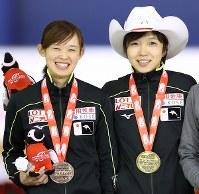 女子500メートルで優勝し、笑顔を見せる小平奈緒(右)と3位の郷亜里砂=カナダ・カルガリーで2017年12月3日、佐々木順一撮影