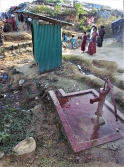 ロヒンギャ難民のキャンプに設置されたトイレの小屋(奥)とすぐ脇に掘られた井戸=難民を助ける会提供