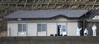 松前小島の宿泊小屋周辺を調査する道警の捜査員ら=北海道松前町の松前小島で4日午後(代表撮影)