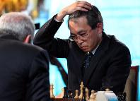 ガルリ・カスパロフさん(左)とチェスで対戦し、熟考する羽生善治さん=東京都港区で2014年11月28日午後0時19分、小川昌宏撮影