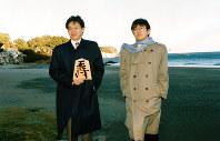 第45期王将戦・第1局 今井浜を背に、記念撮影にこたえる谷川浩司王将(左)と羽生善治名人=1996年1月10日、静岡県河津町で