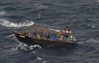 北海道松前町沖で発見された北朝鮮の木造船。乗組員の姿も見える=2017年11月29日午前11時6分、本社機「希望」から