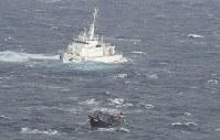北海道松前町沖で発見された北朝鮮の木造船(手前)。後ろは海上保安庁の巡視船=2017年11月29日午前11時8分、本社機「希望」から