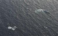 北海道松前町沖の北朝鮮の木造船(右)と警戒する海上保安庁の巡視船=2017年11月29日午前11時22分、本社機「希望」から