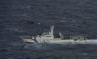 北海道松前町沖で見つかった北朝鮮の木造船(左奥)。手前は海上保安庁の巡視船=2017年11月29日午前11時10分、本社機「希望」から