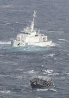 松前町沖で漂流しているのが見つかった北朝鮮の木造船。奥は海上保安庁の巡視船=2017年11月29日午前11時8分、本社機「希望」から