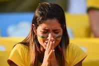 【ブラジル・チリ】PK戦で手をあわせる女性サポーター=2014年6月28日、ゲッティ