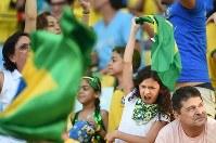【コロンビア・ウルグアイ】マラカナン競技場の大型テレビでブラジルの勝利を見て、ブラジル国旗を振り回して喜ぶ女の子=ブラジル・リオデジャネイロのマラカナン競技場で2014年6月28日、宮間俊樹撮影