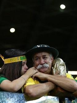【ブラジル・ドイツ】W杯の模型を抱き、涙を流す男性=ブラジル・ベロオリゾンテのミネイラン競技場で2014年7月8日、小出洋平撮影
