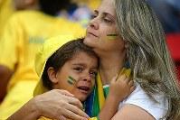【ブラジル・オランダ】試合途中、涙ぐむブラジルサポーターの子ども(左)を抱きしめる女性=2014年7月12日、ゲッティ