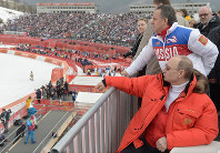 In this file photo taken on March 8, 2014, Russian President Vladimir Putin, foreground, watches downhill ski competition of the 2014 Winter Paralympics in Roza Khutor mountain district of Sochi, Russia, as Russia's sports minister Vitaly Mutko stands behind. (AP Photo/RIA-Novosti, Alexei Nikolsky, Presidential Press Service)