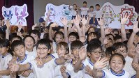 発表された東京五輪・パラリンピックのマスコット最終候補となった3作品の前ではしゃぐ小学生たち=東京都渋谷区で2017年12月7日午前11時20分、渡部直樹撮影