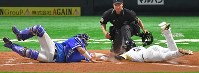 In this Oct. 29, 2017 file photo, SoftBank Hawks' Kenta Imamiya, right, slides to home base during the second game of last season's Japan Series. The initial out call for Imamiya was overturned after a video replay. (Mainichi)