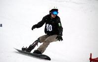 全国障がい者スノーボード選手権で義足を見せながら滑る小栗大地=長野県小谷村で今年2月、谷口拓未撮影