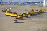 除雪に対応するため、V字形で態勢をとる除雪車=成田空港で