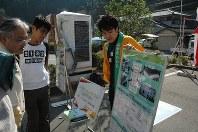 奈良県川上村の祭りに参加し、電気自動車の仕組みを説明する大阪工業大の学生(右)