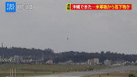 An object, center, appears to fall from a U.S. military helicopter in Ginowan, Okinawa Prefecture, on Dec. 13, 2017. (Photo courtesy of TBS Television via Ryukyu Broadcasting Corp.)