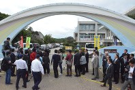 Reporters, local assembly members and others gather outside Ginowan Municipal Futenma No. 2 Elementary School after hearing that an object believed to be from a U.S. military helicopter had fallen on the school grounds, in Ginowan, Okinawa Prefecture, on Dec. 13, 2017. (Mainichi)