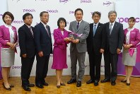 釧路-関空線の開設を発表したピーチの井上慎一CEO(中央右)。高橋はるみ知事(同左)や道東の首長らも同席した=札幌市で