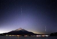 富士山上空の夜空に出現した、ふたご座流星群の流れ星=山梨県山中湖村で2017年12月14日午前0時6分、手塚耕一郎撮影