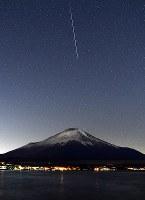 富士山上空の夜空に出現した、ふたご座流星群の流れ星=山梨県山中湖村の山中湖畔で2017年12月14日午前0時6分、手塚耕一郎撮影