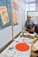 亡父の戦争遺品について説明する勝田栄造さん(左)=富山県入善町入膳の入善まちなか交流施設うるおい館で、青山郁子撮影