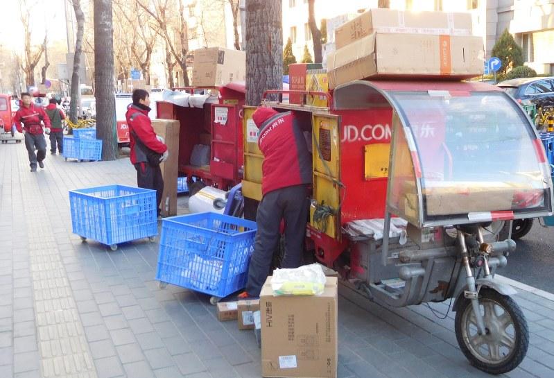 配達用の電動三輪車に荷物を載せる宅配員ら=北京市で2017年12月7日、河津啓介撮影