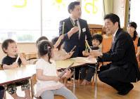 待機児童対策が無償化よりも先だという声は多い。安倍晋三首相(右端)は、保育所を視察したことはあるのだが……