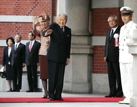 In this Dec. 7, 2017 file photo, Emperor Akihito and Empress Michiko wave at pedestrians on the street after arriving at JR Tokyo Station for a ceremony to celebrate the completion of the Marunouchi square in front of the station. (Pool photo)