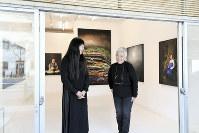 写真家、金サジさん(左)と作品について話す「アートスペース虹」オーナーの熊谷寿美子さん。開放的なガラス扉は画廊のシンボルだった=京都市東山区で2017年12月6日、小松雄介撮影