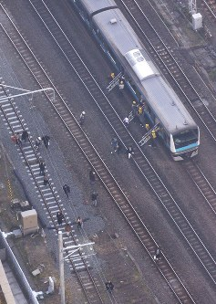 Passengers get off a train on the JR Keihin-Tohoku Line stranded in Kawasaki because of an overhead wire snapping on Dec. 16, 2017. (Mainichi)