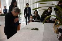 みきおさん一家の写真に手を合わせる母節子さん=世田谷区で