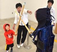 津工高の沢輝龍さん(中央)の指導を受けて剣道を体験する西田絆夏さん(左)=津市一身田上津部田の県総合博物館で