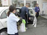 あみの自動車教習所での運転評価を終え、車を降りる男性(中央)。右は同乗していた指導教官、左は作業療法士=京都府京丹後市で2017年11月