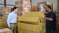 メキシコに向け発送される荷物を確認する通関会社のヘクター・デラミヤ社長(左)