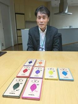 2代目から登場した「ダークミルク」は中央の4種類。「カカオを推しているとはいえ、市場が小さい苦めのダークチョコ(奥の2枚)にこだわりすぎてはだめ」と語る明治の宇都宮洋之・菓子開発研究部長=東京都中央区で2017年12月7日、増田博樹撮影