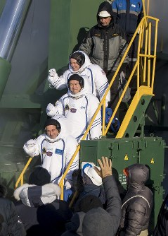 In this photo released by NASA, Expedition 54 flight engineer Scott Tingle of NASA, top, flight engineer Norishige Kanai of Japan Aerospace Exploration Agency (JAXA), middle, and Soyuz Commander Anton Shkaplerov of Roscosmos, bottom, wave farewell prior to boarding the Soyuz MS-07 rocket for launch, at the Baikonur Cosmodrome, Sunday, Dec. 17, 2017, in Kazakhstan. (Joel Kowsky/NASA via AP)