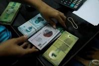 12月15日、慢性的な現金不足に悩むベネズエラの首都カラカスで、貧困地区の地域共同体が、独自通貨「パナル」を発行した(2017年 ロイター/Marco Bello)