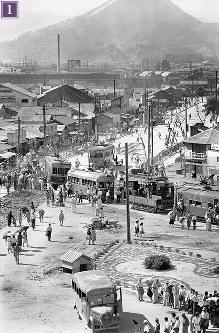 被爆から1年の広島駅舎屋上から南東を撮影(上下2枚つなぎ)。たくさんの人が電車を利用している。画面左端中央の地面が掘り返された部分は、かつて広島駅電停(終点)に向かった線路がはがされた跡。線路は途中でカーブし北方向・駅の正面まで延伸し、広島駅電停(終点)が移設された。南から走ってくる電車は、江波終点付近で被爆(1946年3月復旧)した156号。現在も江波車庫に保存されている。画面左は、中国配電本店前付近で被爆し、現在も「被爆電車」として活躍している651号(1946年3月復旧)。その右隣は、御幸橋付近で被爆した207号(1945年11月復旧)。右から2両目は、資材などを運ぶための無蓋電車の102号。正面は黄金山=広島市松原町(現広島市南区)で1946年7月24日ごろ