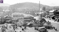 被爆から半年の広島駅前広場南側に広がる露店の闇市。1946年1月10日にパターソン米陸軍長官が広島を視察した際の警備上の理由から、駅前から南側・松原町下の段に移転した。左奥から、住友銀行東松原支店、比治山、猿猴橋、旧新見商店など=広島市松原町(現広島市南区)の広島駅駅舎の屋上から南に向かって撮影1946年2月8日ごろ