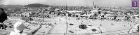 被爆から1年の広島駅駅舎の屋上から南に向かって撮影(3枚つなぎ)。写真中央の更地となっている場所(松原町下の段)を中心に広がっていた露店の闇市は立ち退きが実施され、1946年7月5日に移転が完了。新たに広島郵便局(広島管理部)前広場に木造平屋で460余店を収容する民衆マーケットを建設し、9日に開設式があった画面奥左側から、広島市信用組合猿猴橋支所、住友銀行東松原支店、比治山、猿猴橋、旧新見商店、鉄道病院ボイラー棟、広島東警察署、中国新聞社、福屋新館など。画面左側中央に電車1両(650形のおそらく652号)と線路の工事をしている様子が見える。建築資材を運ぶトロッコがあり、近くに敷石が立てて並べてある。上下線ともプラットフォームができており、車両の左側にはクロスの渡線も。その後ろ手の通りには、「小金寿司」、「朝日書房」、映画(「カサブランカ」1946年6月20日日本公開)、「氷」などの看板がみえる。中央の通り沿いには「日本通運株式会社サービスステーション」「民衆マーケット」「華蓬亭」などの看板が見える=広島市松原町(現広島市南区)で1945年7月24日ごろ