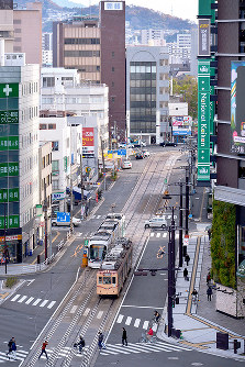 JR広島駅の屋上から南東を望む。再開発で高層ビルが建ち並ぶ南口駅前を路面電車がゆく=広島市南区で2017年12月14日、山田尚弘撮影