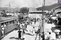 被爆から1年の広島で電車に乗り込むたくさんの人々。手前は千田車庫で被爆した154号(1945年12月復旧)、その後ろは己斐車庫で被爆した204号(1945年11月復旧)。画面中央の地面が掘り返されている部分は、線路が一部はがされた跡。かつての終点へ向かう線路が一部はがされ、向かって左にカーブし、北方向の広島駅正面までレールが延伸され、画面左端の架線用電柱の手前に終点が移設された。2両見える電車は、左が千田車庫で被爆した160号(1945年12月復旧)、右が江波終点付近で被爆した139号と思われる。歩道の木には「広島駅前食堂」の看板が見え、その横の店は「手荷物自転車一時預所」。広島駅正面には「廣島驛HIROSHIMA STATION」の看板が掲げられ、その左手の建物には「JAPAN TRAVEL BUREAU」の看板が見える=広島市松原町(現広島市南区)で1945年7月24日ごろ